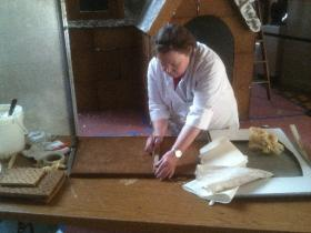 Cheri Vaughn measures and marks a sheet of gingerbread before cutting pieces for the house.