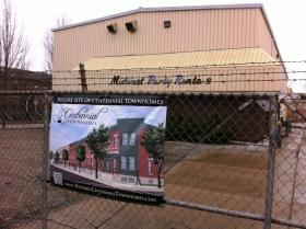 A banner on the gate in front of the vacant Midwest Rentals property shows the city's and neighbors' plan for townhomes.