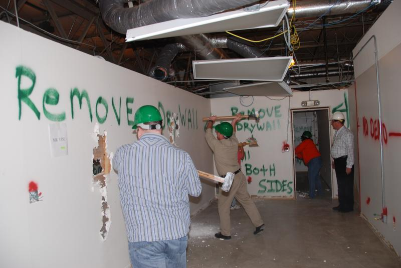 BASi employees lend a hand demolishing walls to make way for a new health and wellness center.