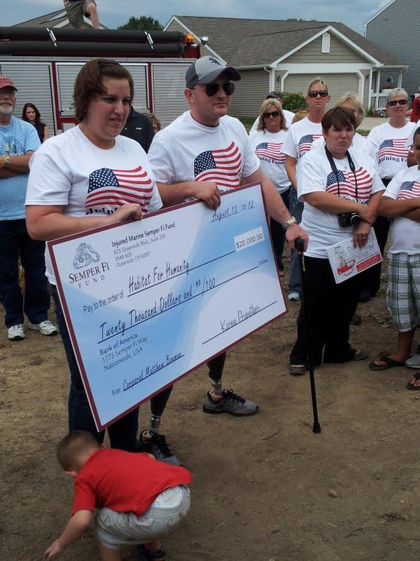 Matt and Paige Bowman accept a check from the Semper Fi Fund