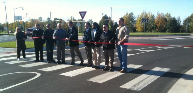 Mayor John Dennis (center) cuts the ribbon during a dedication of the roundabout at Northwestern Avenue and Yeager Road.