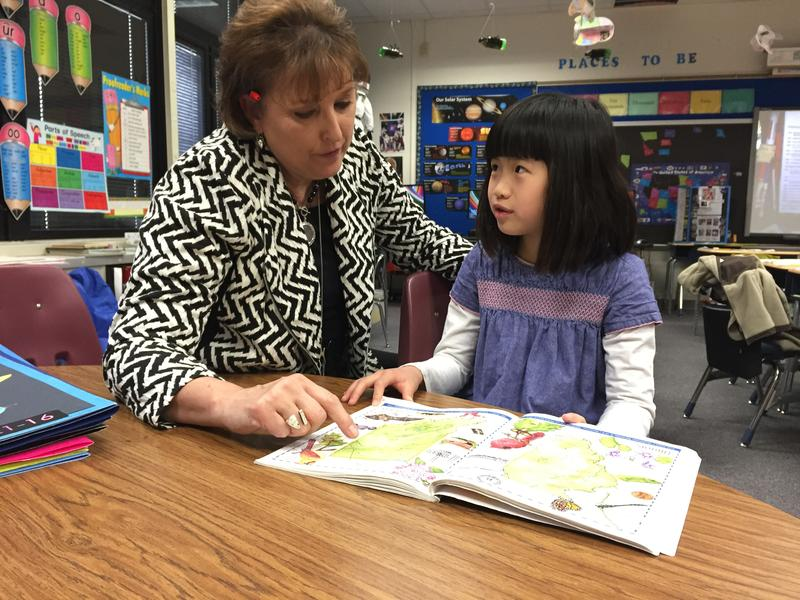 Cumberland Elementary School student Kayla Xu and teacher Maggie Samudio look at a book about state symbols.
