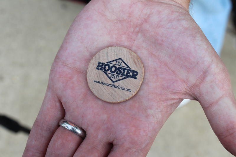 Volunteers give out wooden nickels allowing coach passengers to upgrade to the Hooser State's business class seats.