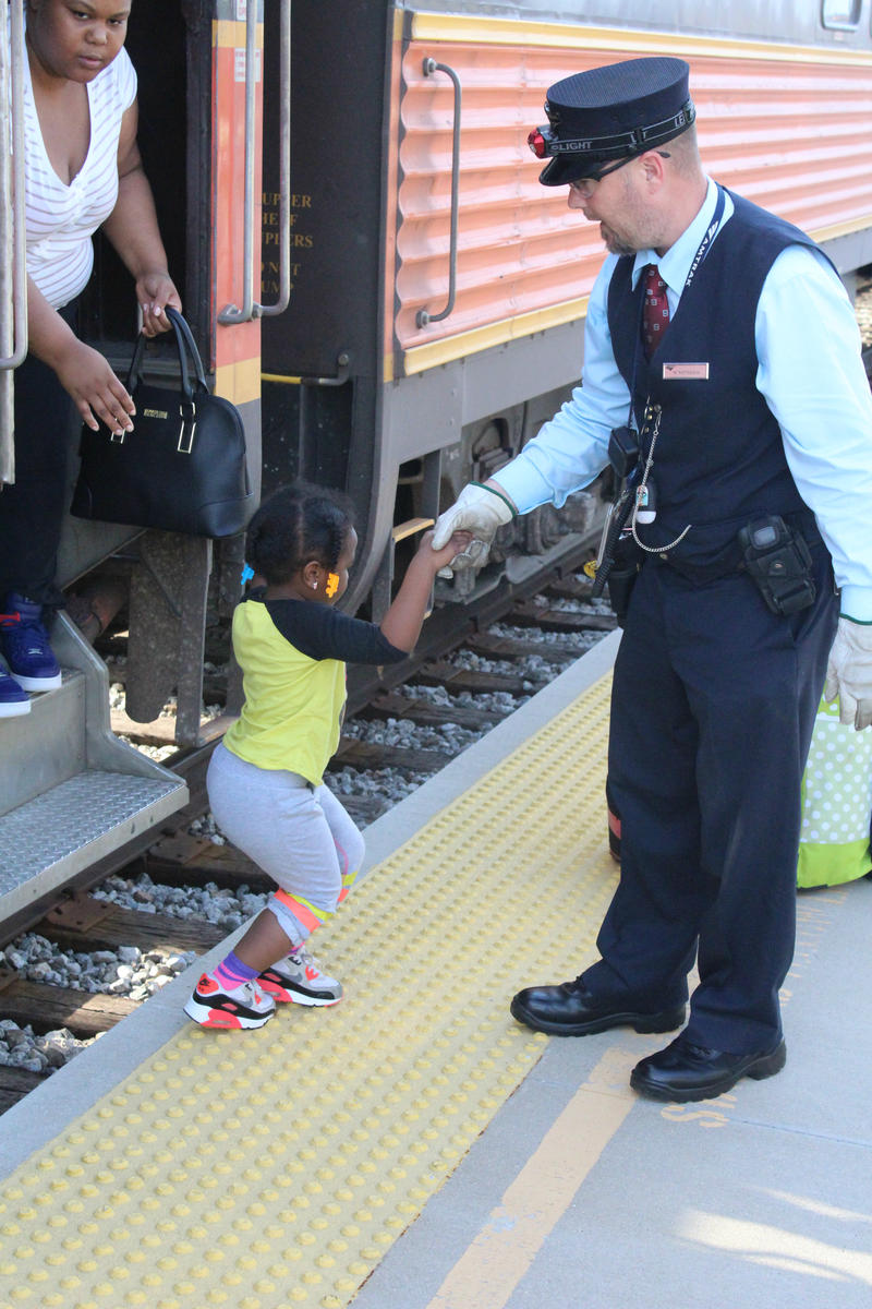 Conductor Matthew Patterson helps passenger Breanna Henderson and her daughter off the train in Dyer.