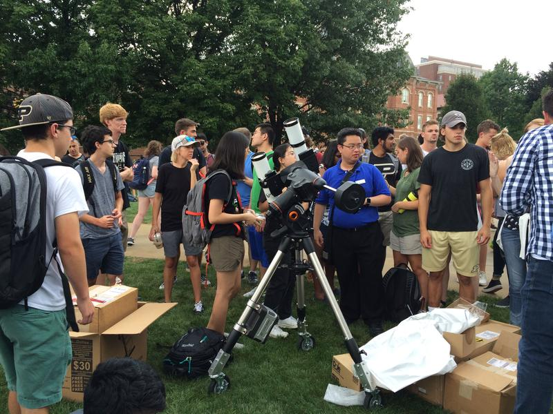 Hongda Zeng with the Purdue Astronomy Club stands beside a high-power telescope.
