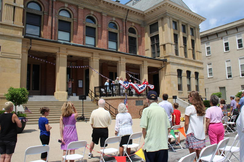Attendees stand during the Pledge of Allegiance Sunday during the clock tower dedication ceremony.