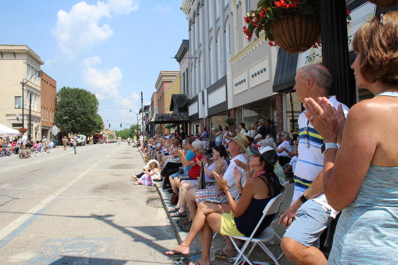 Residents line a shaded street to watch the clock tower dedication ceremony.