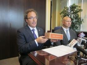 US Attorney William Hochul holds up coin box in discussing plea deal in city parking meter thefts