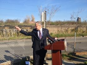 U.S. Senator Charles Schumer at William and Metcalfe in Buffalo Thursday pointing to low clearance at  CSX railroad bridge