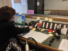 Marie Willet answers phone calls inside the reception area of the Legal Aid Bureau