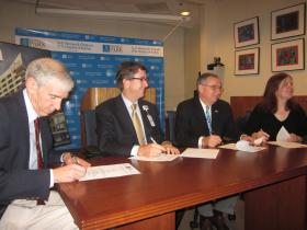 Hospital leaders sign paperwork for the new pediatric care alliance