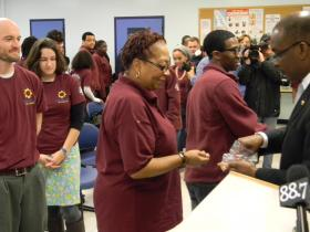 Mayor Brown hands out city pins to new AmeriCorps volunteers.
