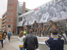Some fans at the game stopped for a look at the recently-erected bronze statues of the famed French Connection outside the arena.