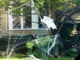 A ghost hangs from a tree in an outside Halloween lawn decoration from a home in Amherst, N.Y.