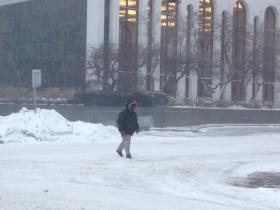 Man crossing the street during the blizzard.