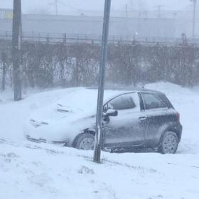 A snow covered vehicle sits in a parking lot near the thruway.