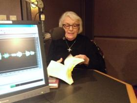 Rosalie Riegle, author, professor and oral historian of nonviolent resisters who serve in jail-time for peace thumbs through her book in the WBFO studio as she discusses her work.