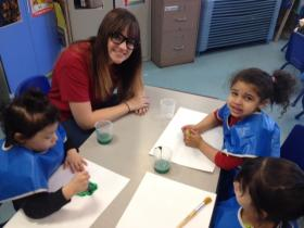 AmeriCorps member Victoria Johns helps preschoolers paint St. Patrick's Day pictures.