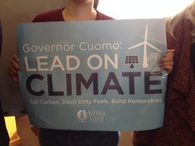 "Wind energy supporter holds sign for ""Turn, Don't Burn"" campaign."