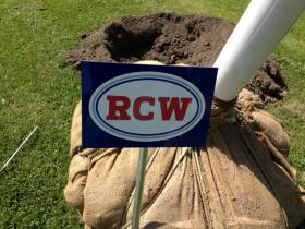 The 'RCW' plaque that can be found in front of a memorial oak tree for Ralph Wilson Jr. in Cazenovia Park.