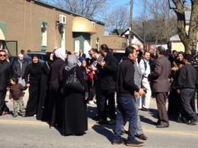 Shammari's family crying as they walk to their cars after the funeral service.