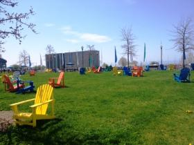 Colorful Adirondack chairs line a grassy park area along Canalside in downtown Buffalo finally giving citizens a chance to enjoy the waterfront.