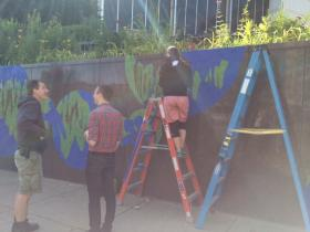 Artists work on public mural made of painter's tape.