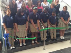 Students cut the ribbon for the opening of the new school building.