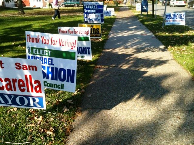 Various campaign lawn signs outside a polling site in the Village of Kenmore