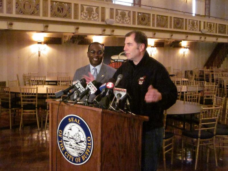 Buffalo Winterfest and Powderkeg Festival organizer Drew Cerza details plans for this weekend's activities.  Buffalo Mayor Byron Brown watches behind him.
