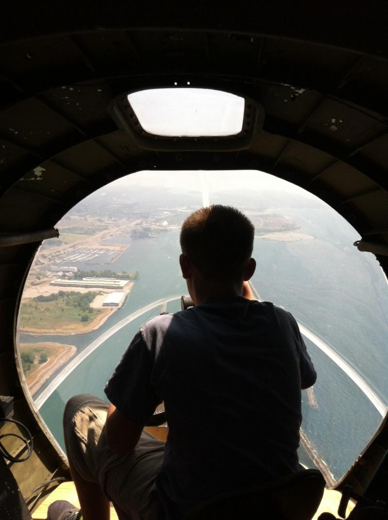 A passenger views the Buffalo waterfront from the glass nose of the B-17.