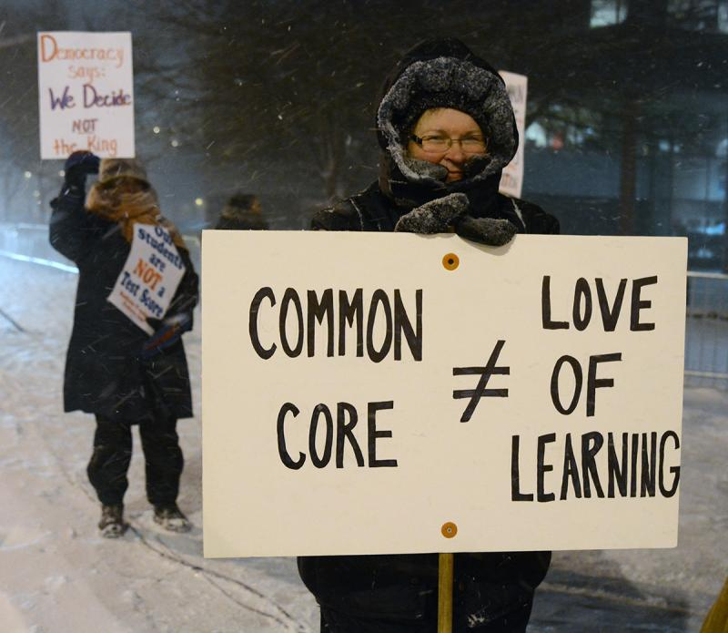 Protestor waves sign in snowy weather against Commono Core