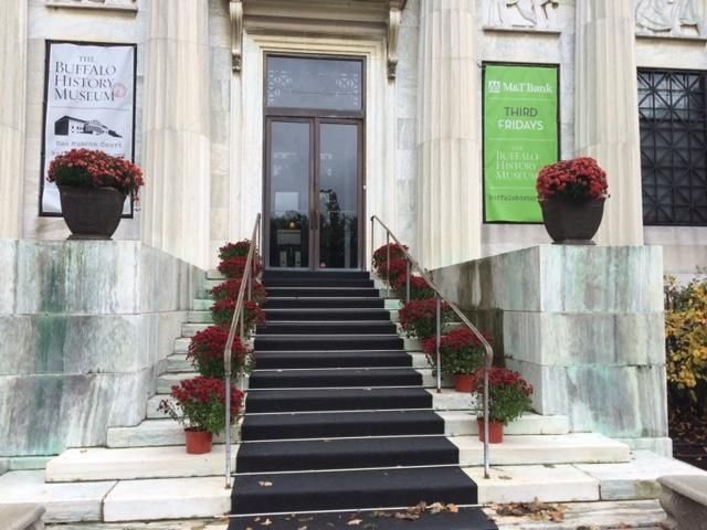 Outside the steps of Buffalo History Museum with red mums in honor of the Russert exhibit opening