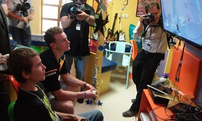 Jack Eichel and a new friend play hockey on a video game system during the Sabres rookie's visit to Roswell Park Cancer Institute.