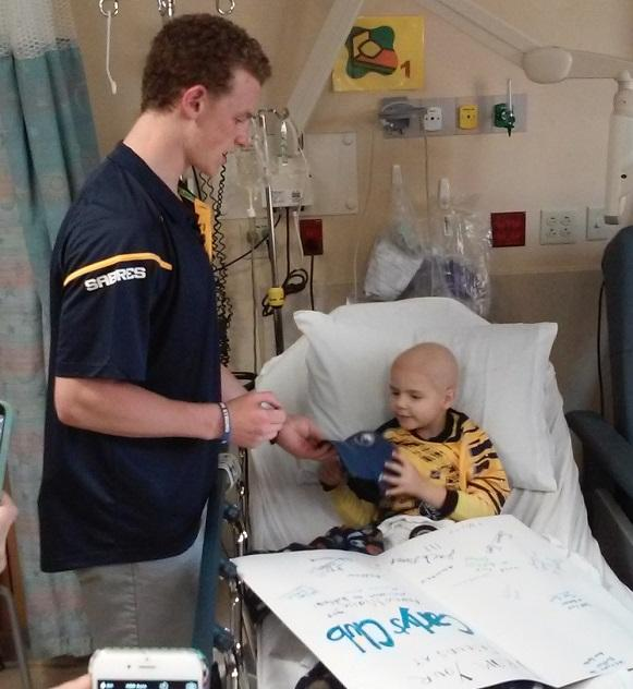 Jack Eichel signs a cap for young Matt, 5, who presented him with a card signed by several patients.