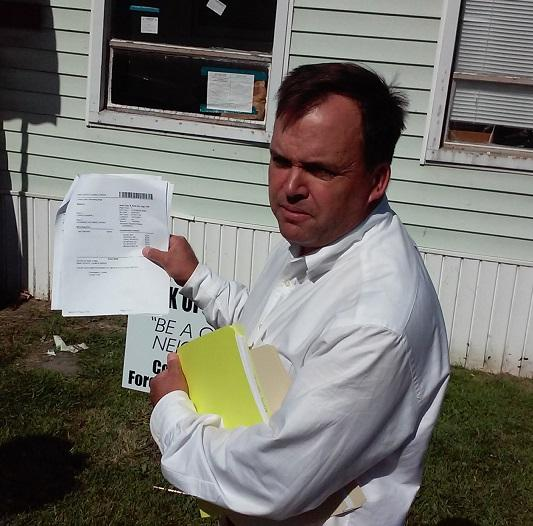 Matthew Fisher of Old First Ward holds paperwork detailing a foreclosure process at 20 Sidway in Buffalo, which began five years ago but has not been completed.