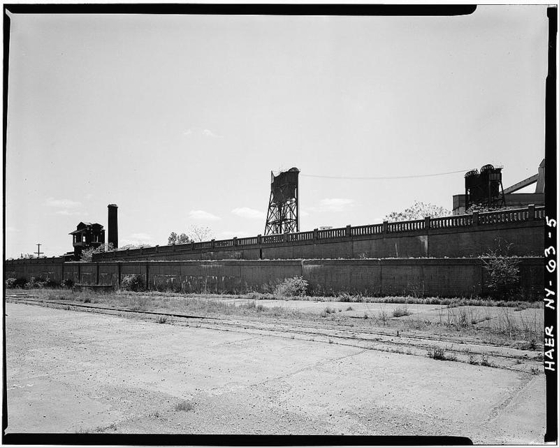 5.View of DL&W toward eastern end of property from South Park Avenue showing concrete access ramp to second level. Signal tower & smoke stack portions of Boiler Room at left; towers of Michigan Avenue Bridge over the Buffalo River in background .