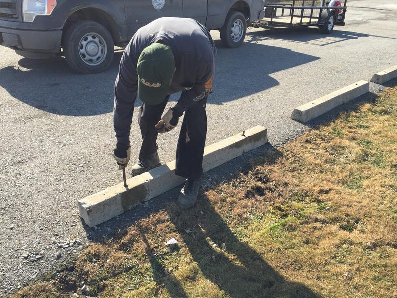 A City of Buffalo employee repairs a parking berm at McCarthy Park