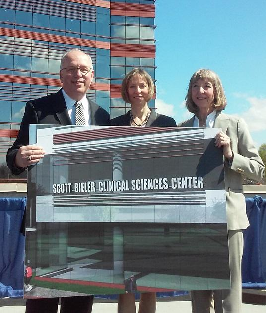 From left to right, Scott Bieler, his longtime partner Kathryn Lasher and Roswell Park Cancer Institute president and CEO Dr. Candace Johnson hold up an image of the sign that will soon identify the newest building on the Roswell Park campus.