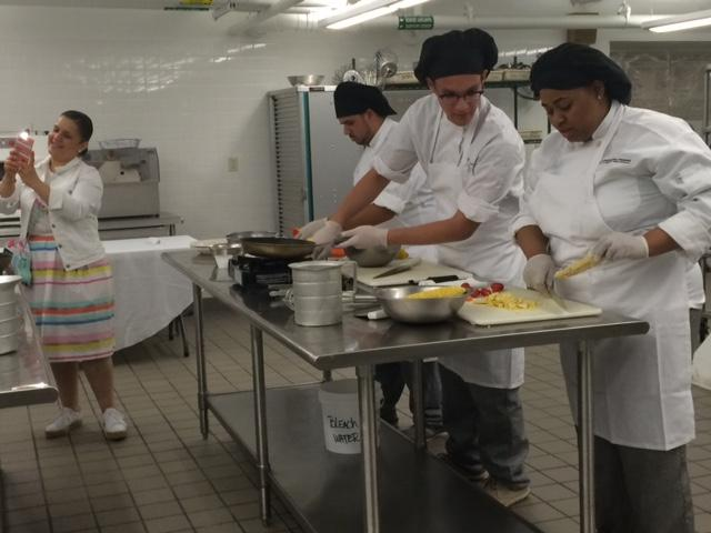 Chef Lizette 'Snap Chat's as she watches Emerson School of Hospitality students.