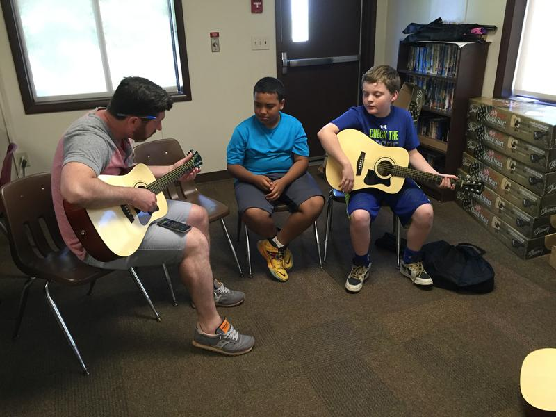 An adult instructor uses a tuning app to prepapre a guitar for young children to practice skills learned at the Valley Community Center.