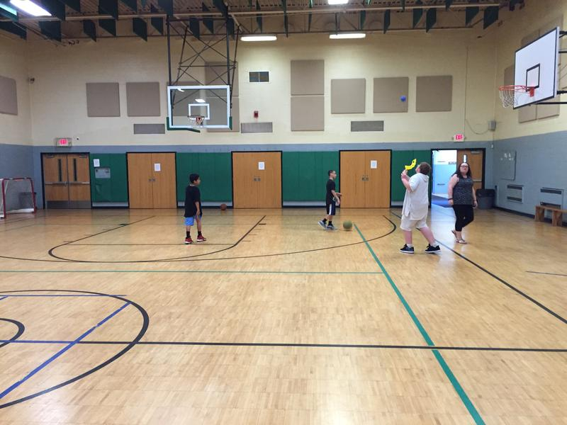 Children play in a gym, with supervision from an adult at the Valley Community Center.