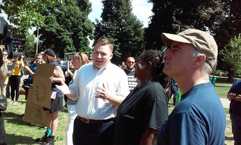 "Erie County Legislator Patrick Burke (center) speaks to activists during a protest against an announced ""White Lives Matter"" rally."