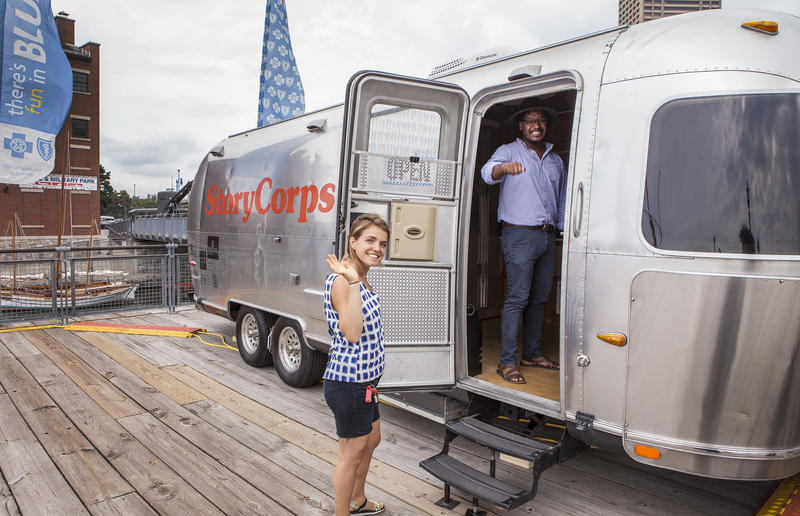 Facilitators Naomi Blech and Felix Lopez welcome visitors to the StoryCorps Mobile Tour Booth at Canalside.
