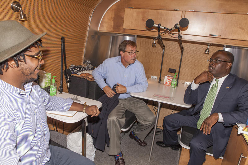 StoryCorps Mobile Tour Facilitator Felix Lopez gives Empire State Development Regional President Sam Hoyt and City of Buffalo Mayor Byron Brown a tour inside the StoryCorps mobile recording booth.