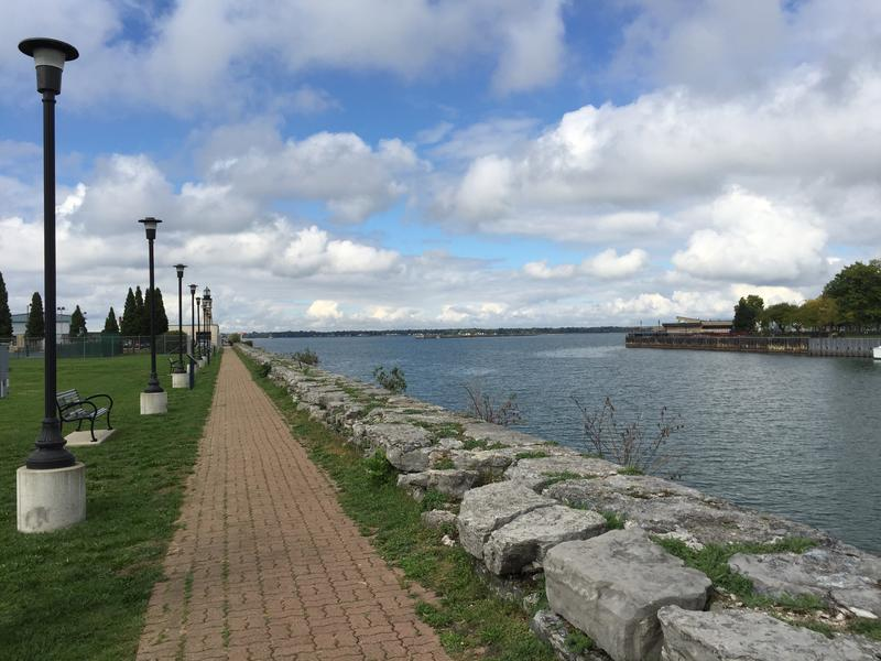 The walkway at Lighthouse Point continues along a worn sea wall, opposite the Erie Basin Marina.