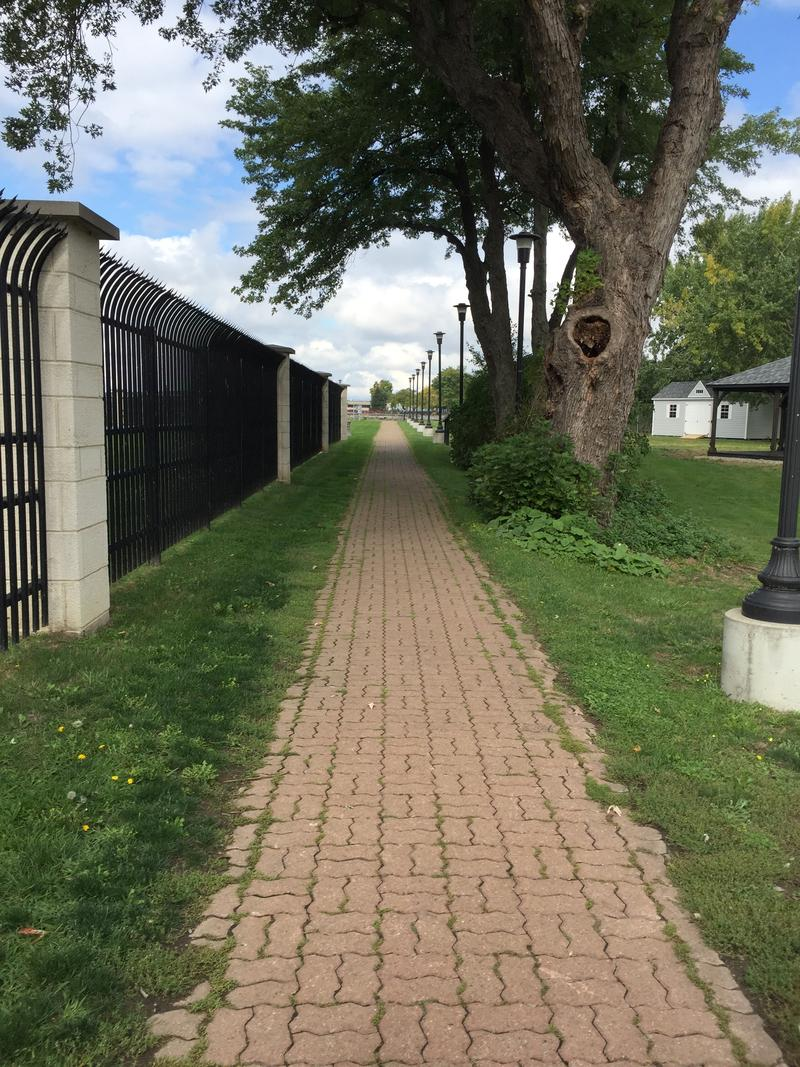 The beginning fo the brick path into Lighthouse Point Park is lined by high sharp fences, protecting the neighborhing U.S. Coast Guard station.