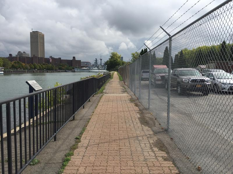 The walkway along the harbor at Lighthouse Point Park is lined with fences - one to protect visitors from the water's edge, the other - topped in razor wire - to protect the neighboring Coast Guard station.