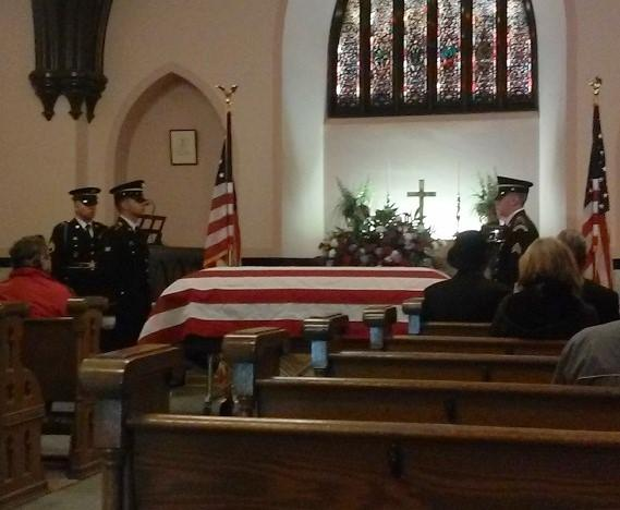 A flag-draped coffin containing the remains of Roy Fink rests inside the chapel before the start of Friday's ceremony.