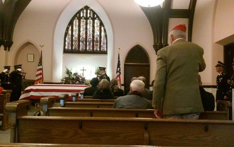 "Retired Erie County Sheriff and Korean War veteran Thomas Higgins dons his red hat and stands during the playing of ""Taps"" inside the chapel."